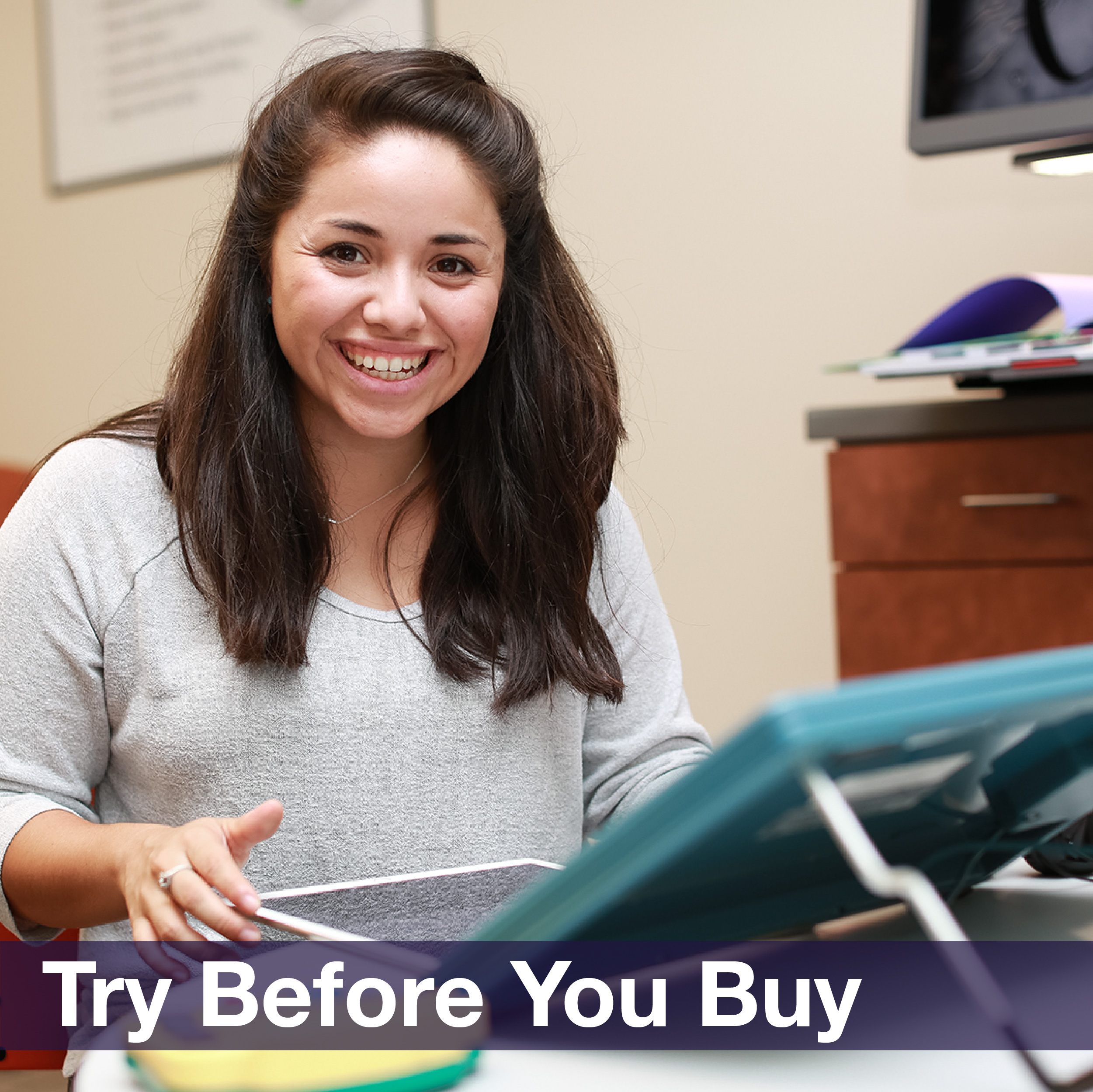"A young woman smiling and using a tablet, accompanied by the phrase ""Try before you buy"""
